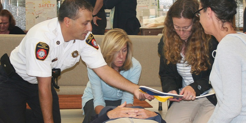 UConn fire department worker in uniform working with three women on safety training