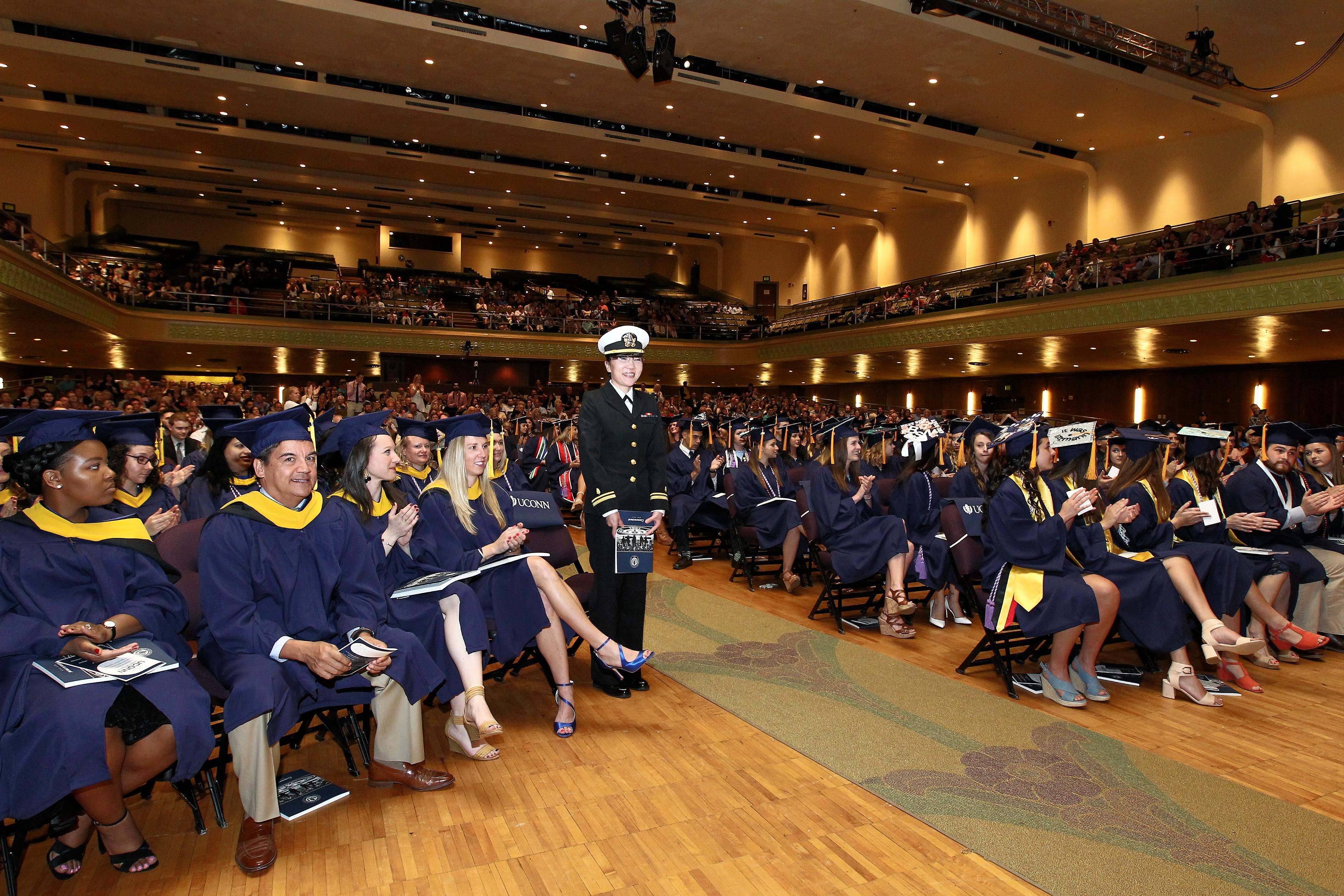 Student in navy uniform surrounded by other students at commencement