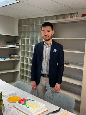 Photo of Christopher Yi standing at a table with a cake