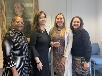 Photo of four women posed together, smiling for the camera