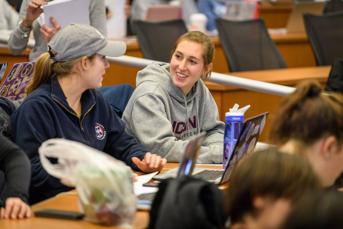 A student speaks with a classmate during a Nursing class in the Widmer Wing of Storrs Hall.