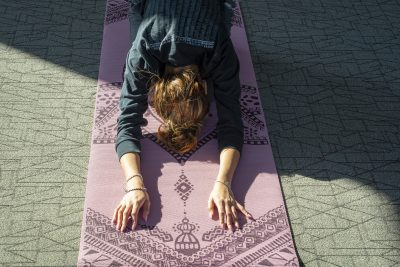 A student rests in child's pose during a yoga and mindfulness class.
