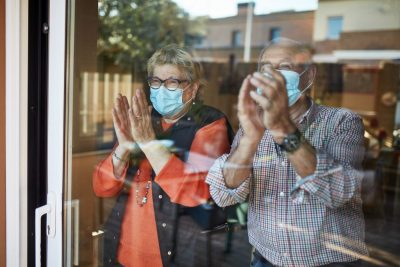 Two older adults are seen through a window, clapping and wearing face masks.